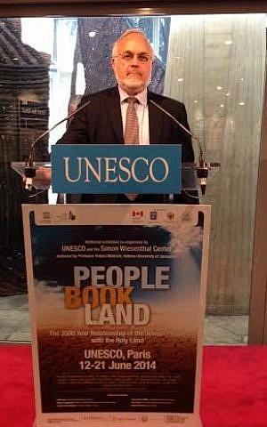 El Rabino del Centro Simon Wiesenthal, Abraham Cooper, habla desde un podio con el nuevo póster de la exhibición, con la referencia a la Tierra de Israel reemplazada por Tierra Santa, el 11 de junio. (Crédito de la foto: Cortesía del Centro Simon Wiesenthal)
