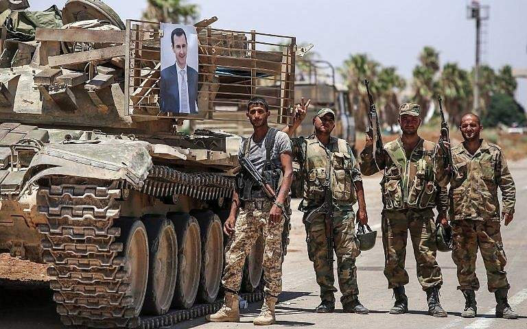 Soldados del régimen sirio se paran junto a la imagen del presidente sirio Bashar Assad colgando de un tanque en el cruce fronterizo de Nassib con Jordania en la provincia sureña de Daraa el 7 de julio de 2018. (AFP Photo / Youssef Karwashan)