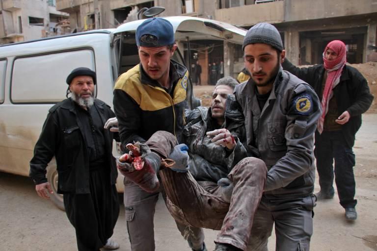 Voluntarios de la Defensa Civil, conocidos como Cascos Blancos, llevan a un hombre herido a un hospital improvisado en la ciudad de Douma, controlada por los rebeldes, tras los ataques aéreos de las fuerzas del régimen en la sitiada región oriental de Ghouta, en las afueras de la capital, Damasco, el 20 de febrero. 2018. (Hamza Al-Ajweh / AFP)