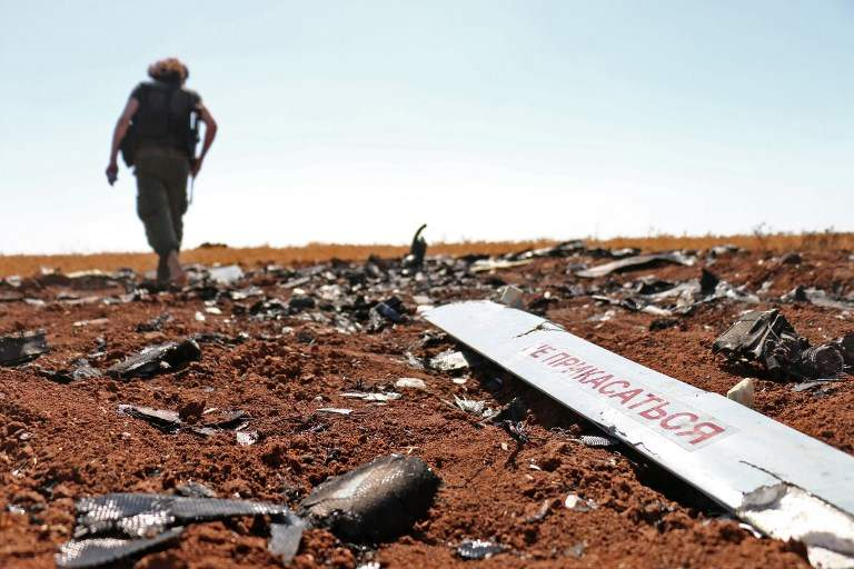 Un combatiente rebelde camina cerca de lo que supuestamente son los restos de un avión no tripulado del régimen sirio que fue derribado por Israel el día anterior, en un campo cerca de Barqah, a unas docenas de kilómetros de la frontera israelí el 12 de julio de 2018. (AFP PHOTO / Ahmad al-Msalam)