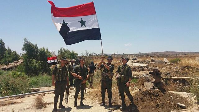 Bandera siria levantada en Quneitra (Foto: AFP)