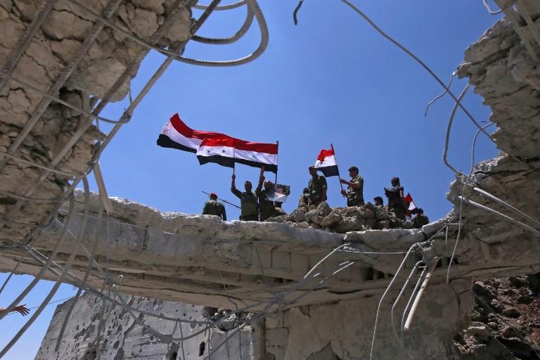 Los soldados de las fuerzas del gobierno sirio ondean sus banderas nacionales después de recuperar la ciudad de Quneitra de los rebeldes, el 19 de julio de 2018. (AFP PHOTO / Youssef KARWASHAN)