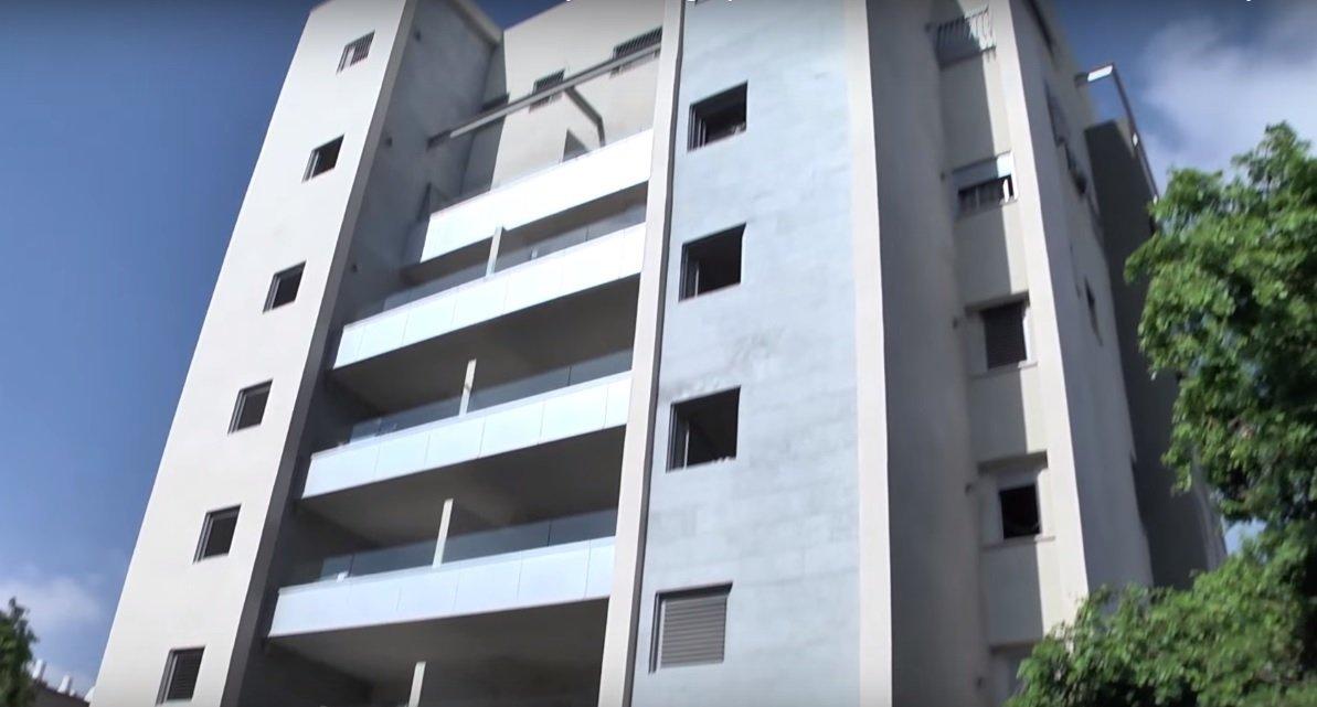 Un edificio de apartamentos en proceso de fortalecimiento.Se pueden ver nuevas habitaciones a prueba de bombas a la derecha e izquierda de los balcones.(Captura de pantalla de YouTube)