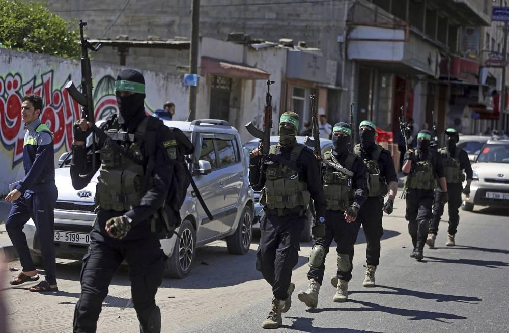 Enmascarados armados de las Brigadas Izzedine al-Qassam, un ala militar del grupo terrorista Hamas, marchan con sus armas durante un simulacro a gran escala en la franja de Gaza, el 25 de marzo de 2018. (AP Photo / Khalil Hamra)