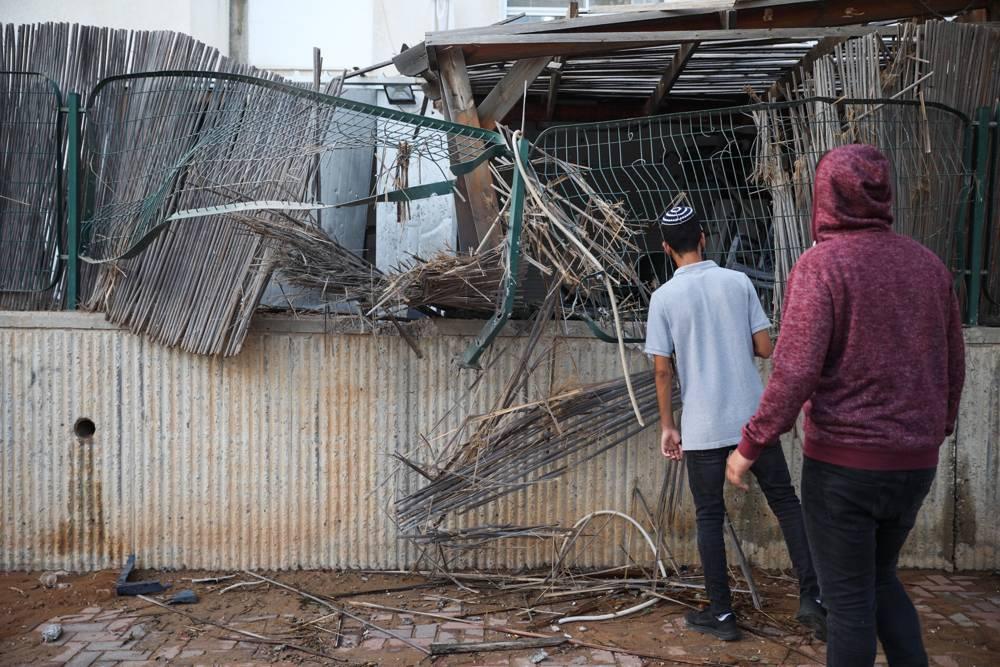 Personas en la escena en que un patio de una casa fue alcanzado por un cohete de Gaza en la ciudad de Sderot, al sur de Israel, el 14 de julio de 2018. (Hadas Parush / Flash 90)
