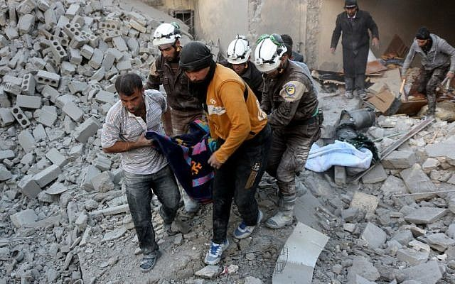 Voluntarios de la defensa civil siria, conocidos como los Cascos Blancos, evacuan a una víctima de los escombros de un edificio después de los ataques aéreos informados en el distrito de al-Hamra controlado por los rebeldes de Alepo el 20 de noviembre de 2016. / AFP PHOTO / THAER MOHAMMED