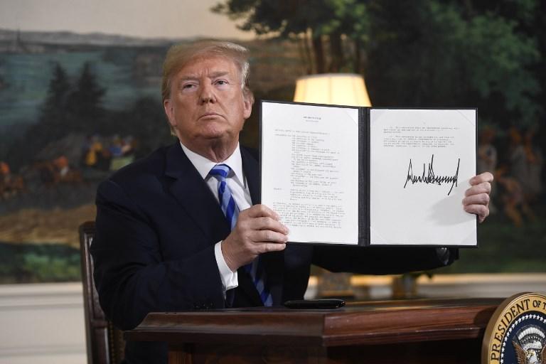El presidente estadounidense Donald Trump firma un documento que restablece las sanciones contra Irán después de anunciar la retirada de Estados Unidos del acuerdo nuclear de Irán, en la sala de recepción diplomática en la Casa Blanca en Washington, DC, el 8 de mayo de 2018. (AFP PHOTO / SAUL LOEB)