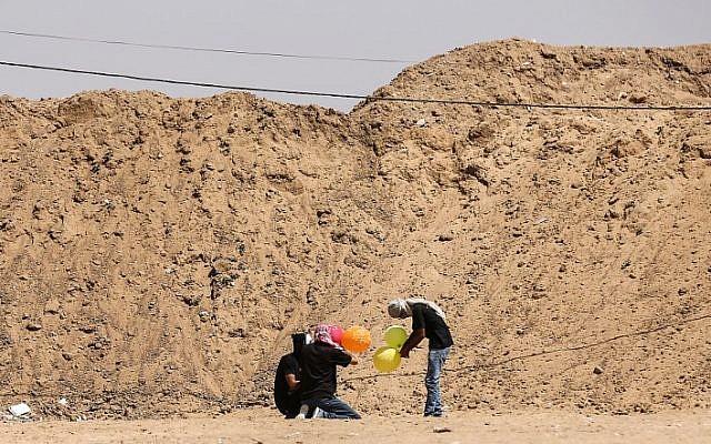 Ilustrativo: los habitantes de Gaza cargan globos con material inflamable para volar hacia Israel, en la frontera entre Israel y Gaza en al-Bureij, en el centro de la Franja de Gaza el 14 de junio de 2018. (AFP / Hams Mahmud)
