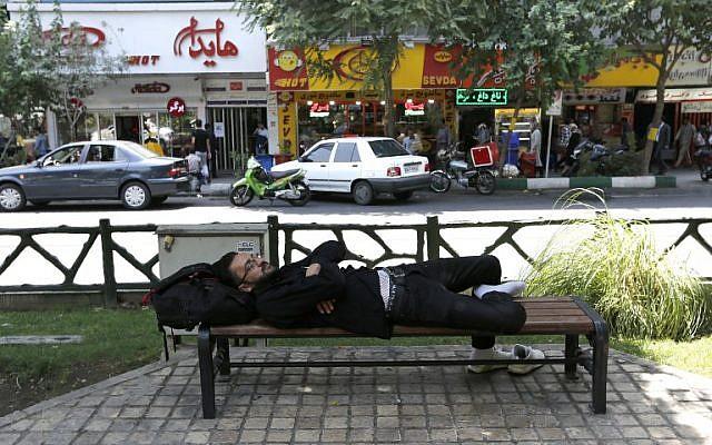 Un hombre toma una siesta en un banco en la capital iraní, Teherán, el 6 de agosto de 2018.  (AFP / ATTA KENARE)
