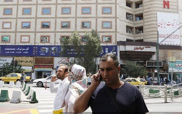 Un hombre habla por su teléfono móvil cuando cruza una calle en un distrito comercial en el centro de Teherán el 6 de agosto de 2018. (AFP PHOTO / ATTA KENARE)