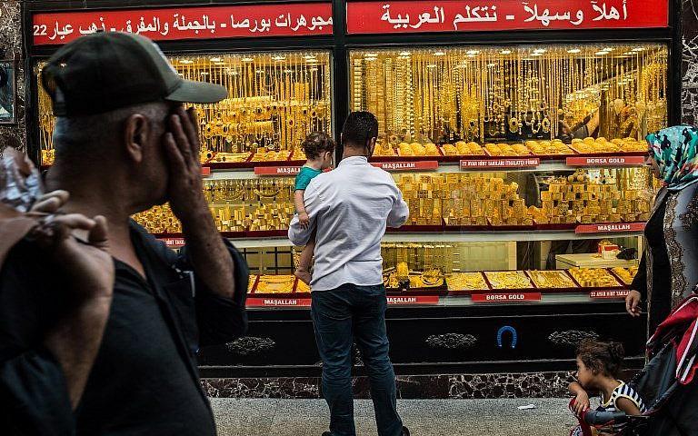 La gente pasa frente a una joyería donde se exhiben brazaletes de oro en Estambul el 8 de agosto de 2018. (AFP Photo / Yasin Akgul)