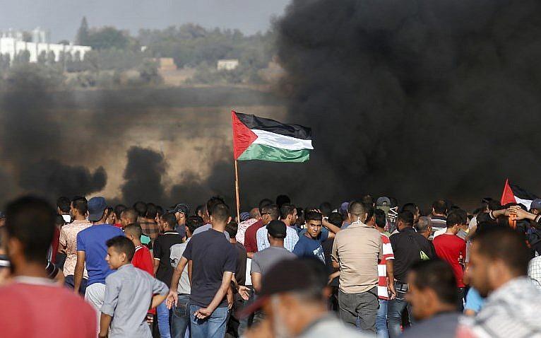 Los manifestantes palestinos agitan su bandera mientras se reúnen durante una manifestación en la frontera entre Israel y Gaza, en Khan Younis, en el sur de la Franja de Gaza, el 10 de agosto de 2018. (AFP PHOTO / Said KHATIB)