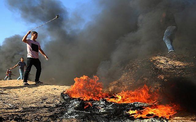 Un palestino usa un tirachinas junto a la quema de neumáticos durante los enfrentamientos en la frontera entre Israel y Gaza, al este de Khan Yunis en el sur de la Franja de Gaza el 10 de agosto de 2018. (AFP Photo / Said Khatib)