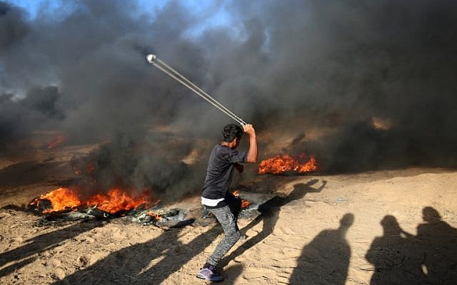Un manifestante palestino usa un tirachinas junto a neumáticos en llamas durante una manifestación en la frontera entre Israel y Gaza, al este de Khan Yunis en el sur de la Franja de Gaza el 10 de agosto de 2018. (AFP PHOTO / SAID KHATIB)