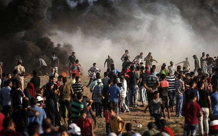 El humo del incendio de un neumático se eleva cuando los palestinos protestan cerca de la frontera con Israel, al este de la ciudad de Gaza, el 17 de agosto de 2018 (AFP PHOTO / MAHMUD HAMS)