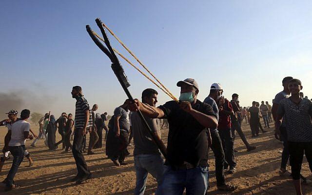 Un manifestante palestino utiliza un tirachinas para arrojar piedras a las fuerzas israelíes durante una manifestación en la frontera entre Israel y Gaza, al este de Khan Yunis en el sur de la Franja de Gaza el 24 de agosto de 2018. (AFP PHOTO / SAID KHATIB)