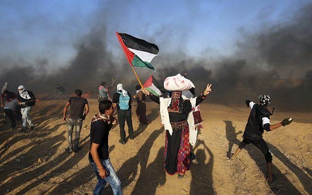 Los manifestantes palestinos arrojan piedras a las fuerzas israelíes mientras un hombre ondea la bandera nacional durante una manifestación en la frontera entre Israel y Gaza, al este de Khan Younis en el sur de la Franja de Gaza el 24 de agosto de 2018. (AFP PHOTO / SAID KHATIB)