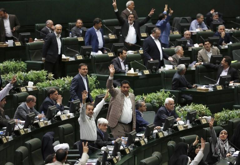 Los miembros del Parlamento iraní hacen gestos mientras el presidente Hassan Rouhani (no en la foto) habla en la capital, Teherán, el 28 de agosto de 2018. (AFP PHOTO / ATTA KENARE)