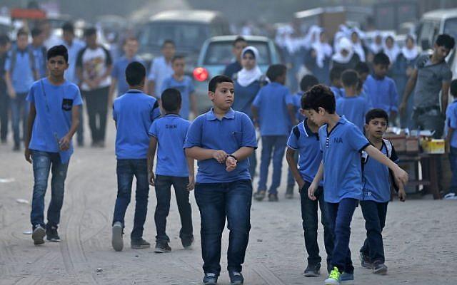 Los alumnos se reúnen frente a una escuela administrada por la Agencia de las Naciones Unidas para los Refugiados Palestinos (UNRWA) en la ciudad de Gaza el 29 de agosto de 2018, el primer día de clases después de las vacaciones de verano. (AFP PHOTO / Mahmud Hams)