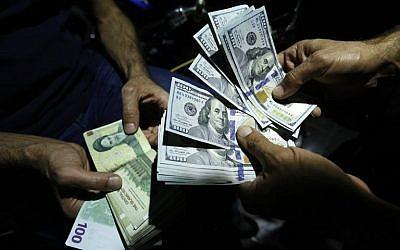 En esta foto del 8 de agosto de 2018, un hombre intercambia Riales iraníes por dólares estadounidenses en una tienda de cambio en la capital iraní, Teherán. (AFP Photo / Atta Kenare)