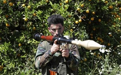 Un combatiente de Hezbolá es visto de pie en atención en un campo naranja cerca de la ciudad de Naqura en la frontera libanesa-israelí el 20 de abril de 2017. (AFP PHOTO / JOSEPH EID)