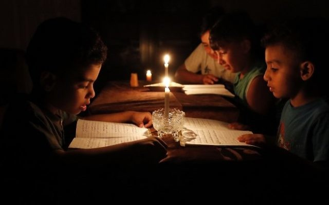 Una imagen tomada el 13 de junio de 2017 muestra a los niños palestinos en casa leyendo libros a la luz de las velas debido a la escasez de electricidad en la ciudad de Gaza. (AFP / THOMAS COEX)