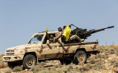 Una fotografía tomada el 26 de julio de 2017 durante un recorrido guiado por el movimiento libanés chiita Hezbollah muestra a los miembros del grupo manejando un arma antiaérea montada en una camioneta en una zona montañosa alrededor de la ciudad libanesa de Arsal a lo largo de la frontera con Siria. (AFP PHOTO / ANWAR AMRO)