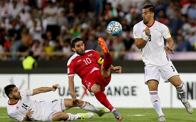 Ehsan Hajsafi (R) y Ali Karimi (L) de Irán luchan por el balón contra el sirio Firas Mohamad Alkhatib durante el partido de clasificación entre Irán y Siria en el Estadio Azadi en Teherán el 5 de septiembre de 2017. (AFP PHOTO / ATTA KENARE)