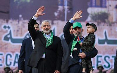 El líder de Hamas Ismail Haniyeh (L) y el líder de Hamas en la Franja de Gaza Yahya Sinwar saludan durante un mitin que marca el 30 aniversario de la fundación del movimiento terrorista islamista en la ciudad de Gaza el 14 de diciembre de 2017. (Mohammed Abed / AFP)