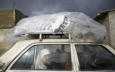 Una mujer palestina viaja en un automóvil después de recoger la ayuda proporcionada por la agencia de la ONU para los refugiados palestinos UNWRA, en la ciudad de Gaza el 17 de enero de 2018. (AFP PHOTO / MOHAMMED ABED)