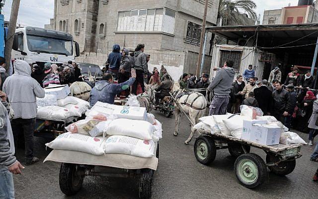 Los palestinos recogen paquetes de ayuda en un centro de distribución de alimentos de las Naciones Unidas en Khan Yunis, al sur de la Franja de Gaza, el 28 de enero de 2018. (Said Khatib / AFP)
