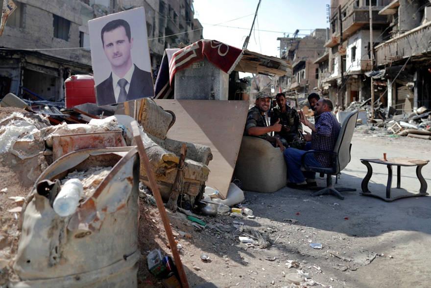 Soldados sirios portan un puesto de control con una imagen del presidente Bashar Assad en el campo de refugiados palestinos de Yarmuk, en Damasco, el 16 de julio de 2018. Hassan Ammar / AP