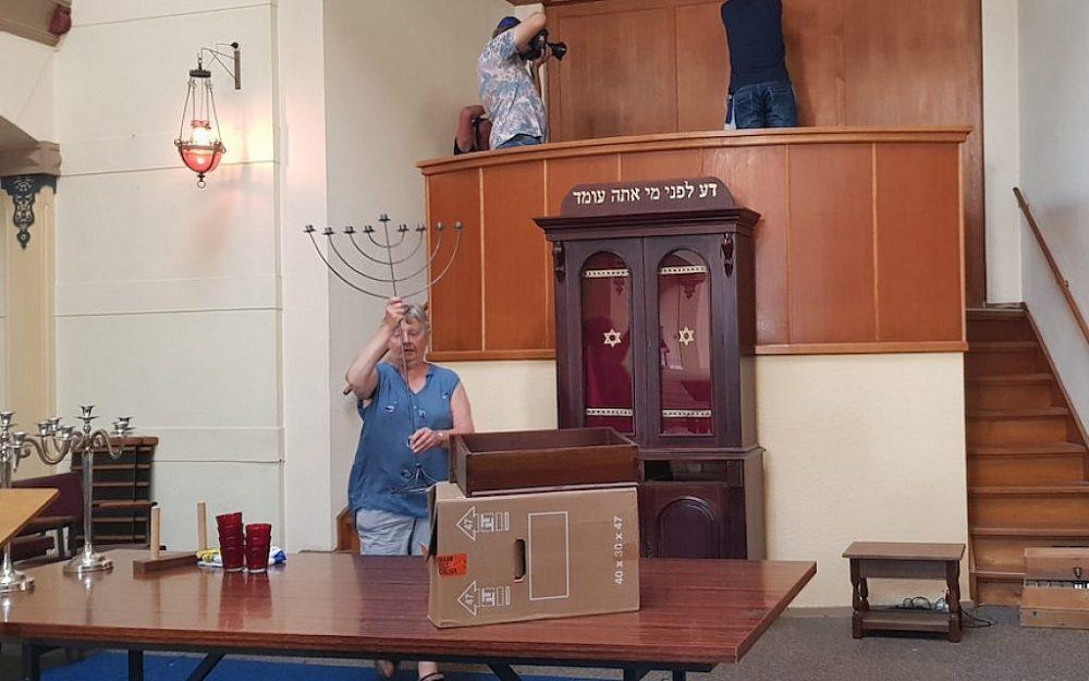 Un congregante ayuda a empacar las pertenencias de la sinagoga, el 30 de julio de 2018. (Cnaan Liphshiz)