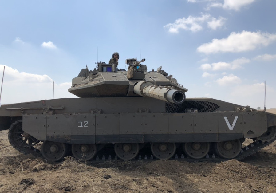 Un soldado se sienta encima de un tanque FDI Merkava durante un simulacro en el norte de Israel