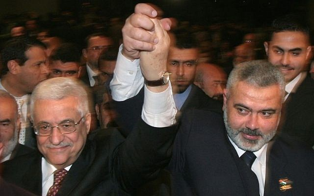 El presidente de la Autoridad Palestina Mahmoud Abbas, izquierda, y luego el primer ministro de Hamas, Ismail Haniyeh, levantan sus brazos mientras avanzan entre la multitud en una sesión especial del parlamento en la ciudad de Gaza, 17 de marzo de 2007. (AP / Hatem Moussa / Archivo )