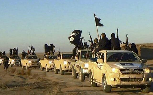 En esta foto de archivo sin fecha publicada por un sitio web militante, que se ha verificado y es coherente con otros informes de AP, jihadistas del grupo Estado Islámico levantan sus armas y ondean sus banderas en sus vehículos en un convoy a Irak, en Raqqa, Siria. . (Sitio web militante a través de AP, archivo)