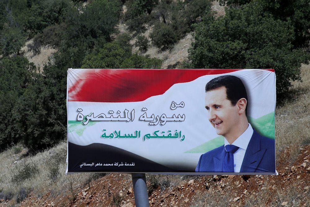 """Un cartel del presidente sirio, Bashar Assad, en árabe, que dice """"Bienvenido en la victoriosa Siria"""", se exhibe en la frontera entre Líbano y Siria, el 20 de julio de 2018. (Hassan Ammar / AP)"""