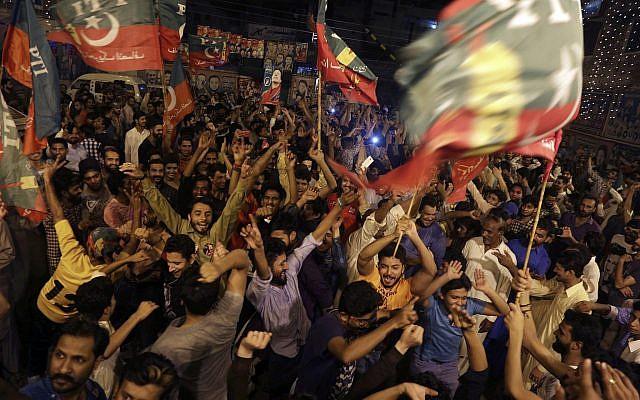 Los partidarios del político paquistaní Imran Khan, jefe del partido Tehreek-e-Insaf de Pakistán, celebran los resultados anunciados por los canales de televisión que indican el éxito de sus candidatos en las elecciones parlamentarias en Islamabad, Pakistán, el 25 de julio de 2018. (AP Photo / KM Chaudary )