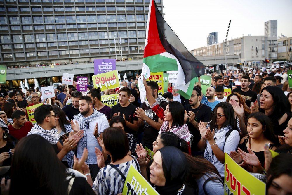 Los árabes israelíes sostienen una bandera palestina durante una protesta contra el proyecto de ley de la nación judía en Tel Aviv, Israel, el sábado 11 de agosto de 2018. (AP / Ariel Schalit)