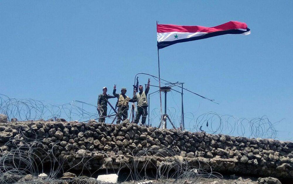 En este martes, 17 de julio de 2018, foto, publicada por la agencia oficial de noticias siria SANA, las tropas sirias muestran el letrero de la victoria junto a la bandera siria en Tell al-Haara, la colina más alta de la provincia suroccidental de Daraa, Siria. (SANA vía AP)