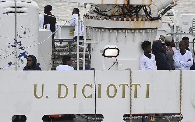 Los inmigrantes se paran en la cubierta del barco de la Guardia Costera italiana Diciotti, amarrado en el puerto de Catania, el 21 de agosto de 2018 (AP Photo / Salvatore Cavalli)