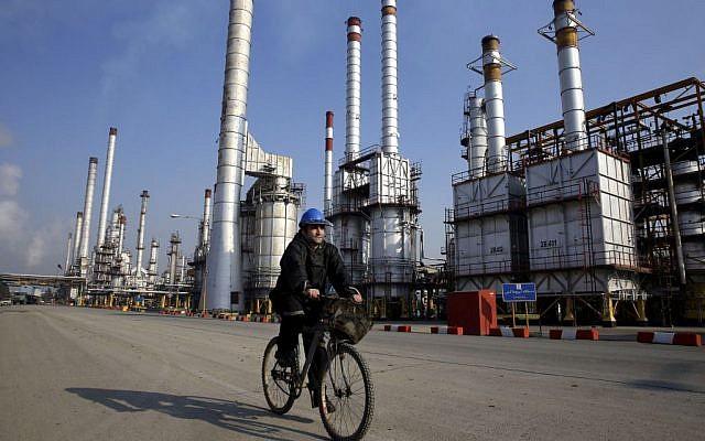 Un trabajador petrolero iraní monta su bicicleta cerca de una refinería de petróleo al sur de la capital, Teherán, 22 de diciembre de 2014. (AP / Vahid Salemi)