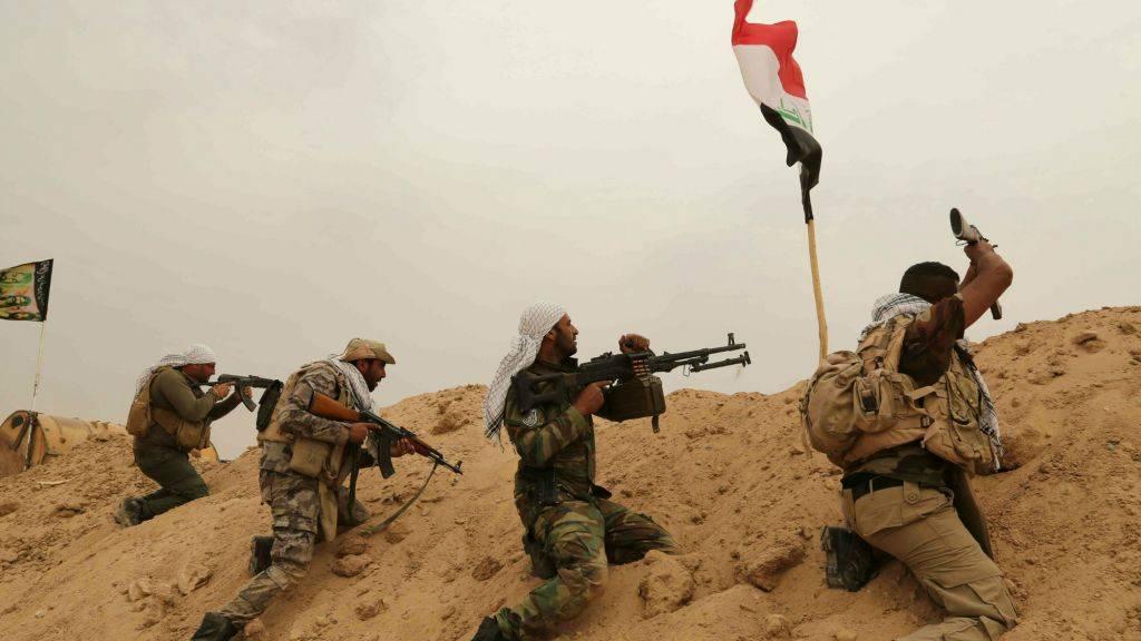 Combatientes de las Brigadas Badr de la milicia chiíta con combatientes del Estado Islámico en primera línea en las afueras de Fallujah en la provincia de Anbar, Iraq, 1 de junio de 2015. (AP / Hadi Mizban)