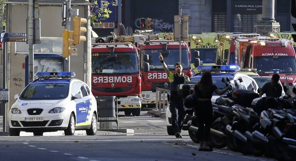 Un oficial de policía hace un gesto mientras bloquea una calle después de un ataque terrorista en el que una furgoneta blanca saltó la acera en el histórico barrio de Las Ramblas, en Barcelona, España, el 17 de agosto de 2017. Manu Fernández / AP)