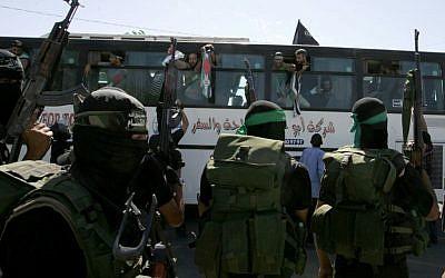 Miembros de Hamas observan autobús que transportaba prisioneros palestinos llega al cruce de Rafah con Egipto en el sur de la Franja de Gaza el 18 de octubre de 2011. (Abed Rahim Khatib / Flash 90)