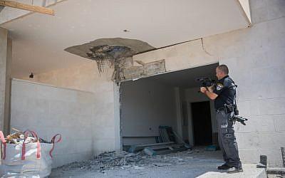 Un oficial de policía inspecciona el daño a un sitio de construcción en la ciudad de Sderot, en el sur de Israel, cerca de la frontera de Gaza después de un lanzamiento de cohete, el 9 de agosto de 2018. (Yonatan Sindel / Flash90)