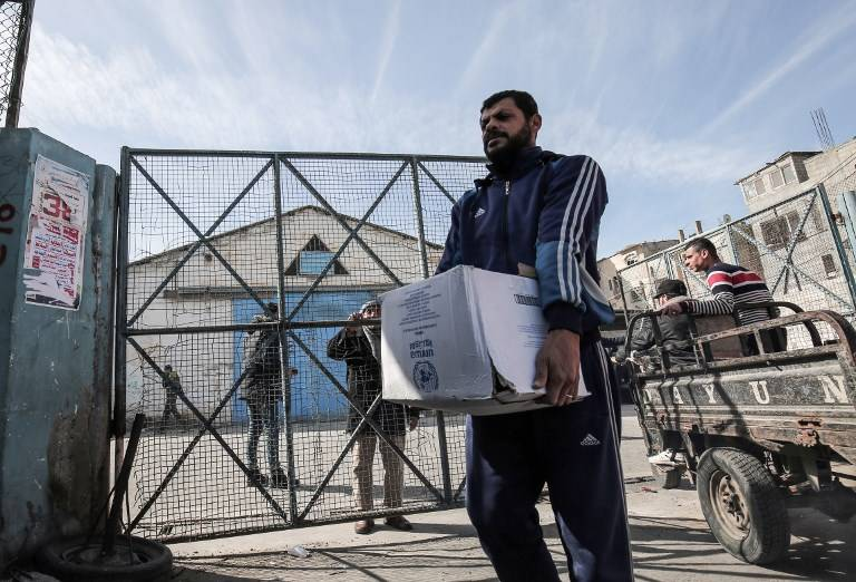 Árabe con estatus de refugiado palestino recoge paquetes de ayuda en un centro de distribución de alimentos de las Naciones Unidas en Rafah, en el sur de la Franja de Gaza, el 21 de enero de 2018. (AFP / Said Khatib)