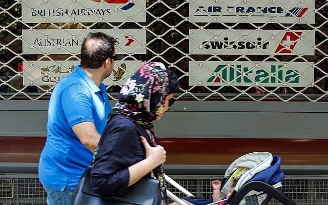 Una familia iraní pasa frente a la ventana cerrada de las oficinas cerradas de una agencia de viajes que muestra los logotipos de varias aerolíneas en la capital, Teherán, el 24 de agosto de 2018. (AFP Photo / Stringer)
