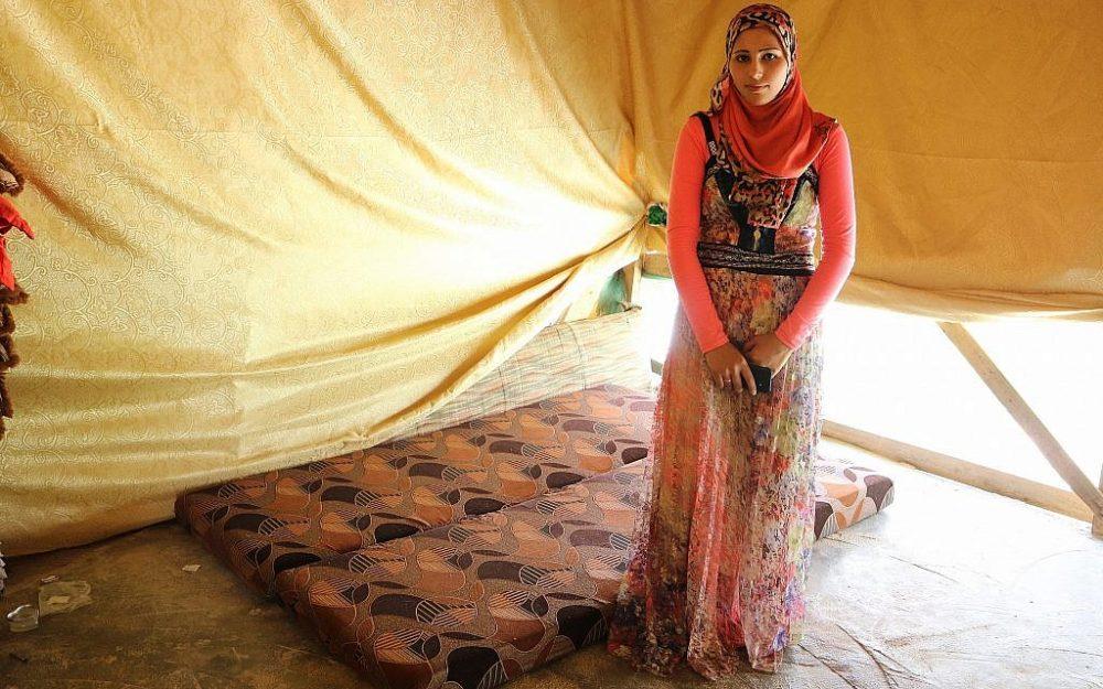Fadia Ammar Al Mohamad, que no conoció a su marido hasta el día de su boda, se encuentra junto a la cama en la que duermen en su tienda de campaña. (Lisa Khoury / Times of Israel)