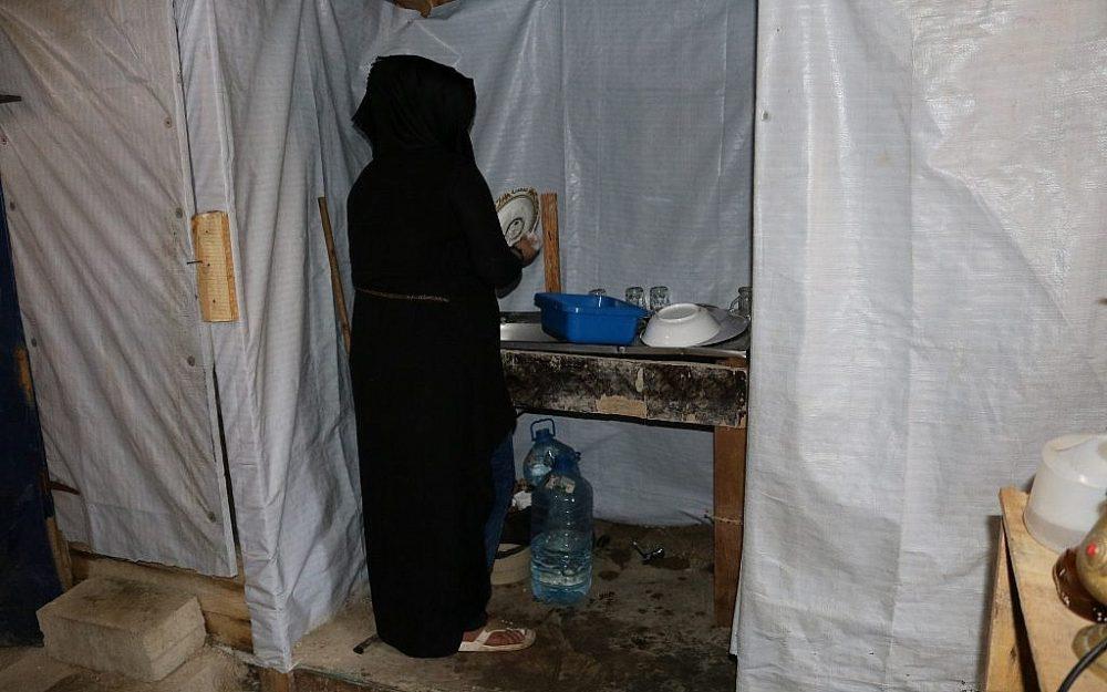 Suzanne Farrah lava los platos dentro de la casa de su familia. Al igual que Halima, se considera una pena por dejar a su marido y apenas sale de la tienda. (Lisa Khoury / Times of Israel)